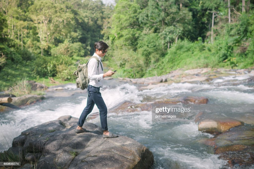 Businessman with backpack and laptop and phone at  waterfall  the forest. : Photo