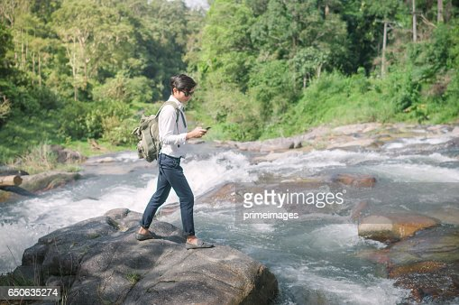 Businessman with backpack and laptop and phone at  waterfall  the forest. : Bildbanksbilder