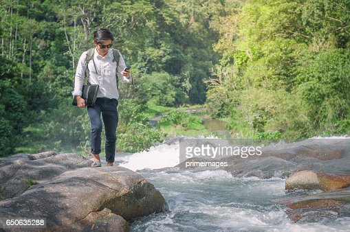 Businessman with backpack and laptop and phone at  waterfall  the forest. : Stock-Foto