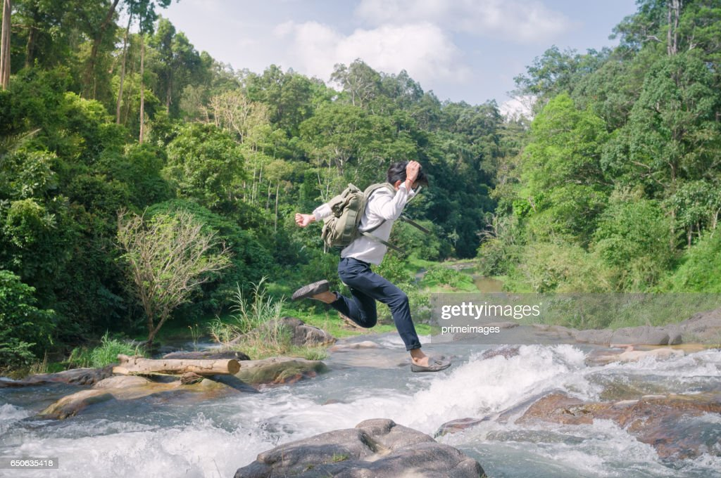 Businessman with backpack and laptop and phone at  waterfall  the forest. : Stock Photo
