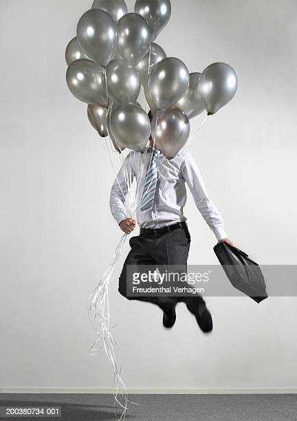Businessman with balloons jumping