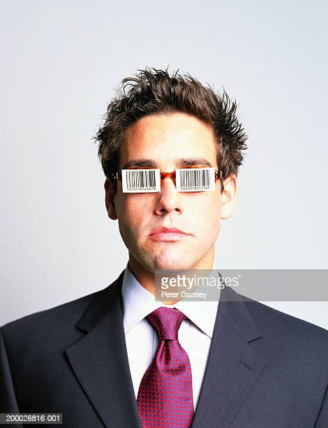 Businessman with barcodes stuck over spectacles, portrait