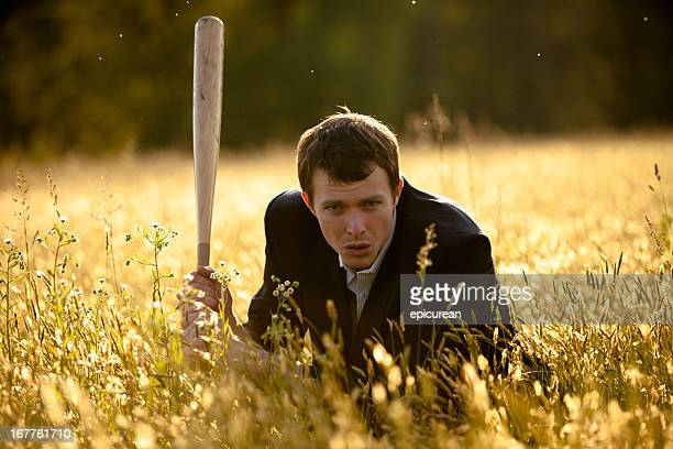 Businessman with baseball bat in field