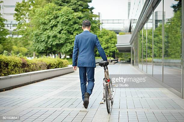 Businessman with bicycle in urban park