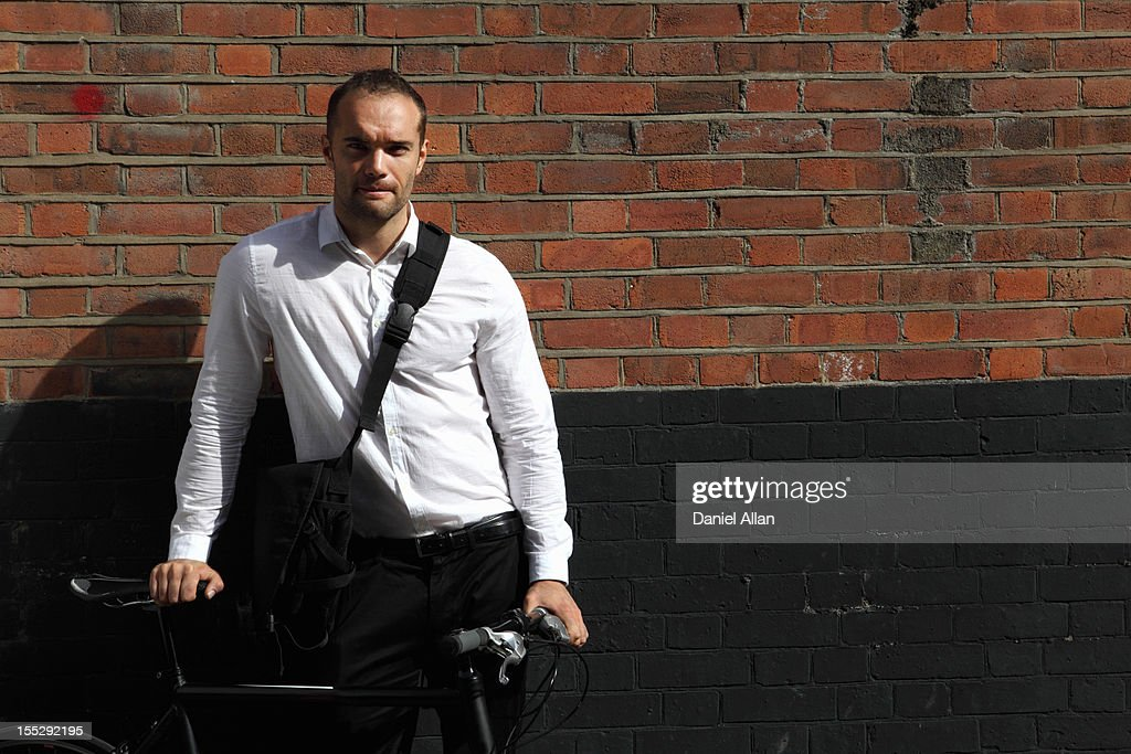 Businessman with bicycle on city street : Stock Photo