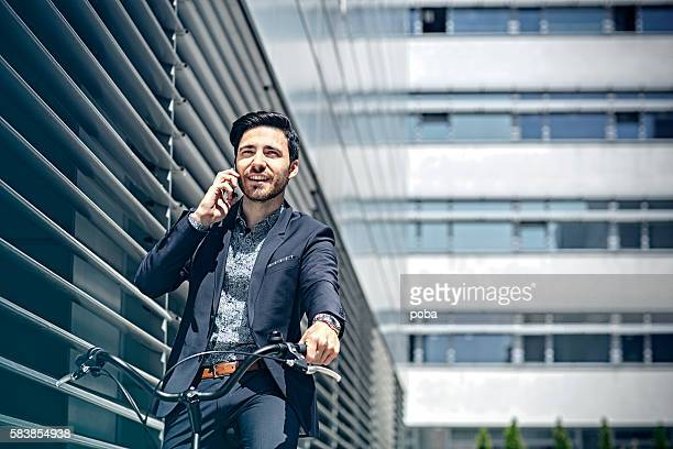 Businessman with bicycle talking on cell phone
