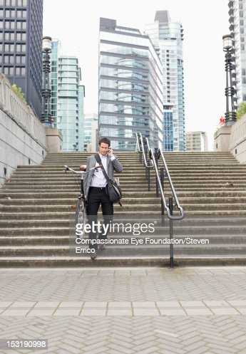 Businessman with bicycle using mobile phone : Stock Photo