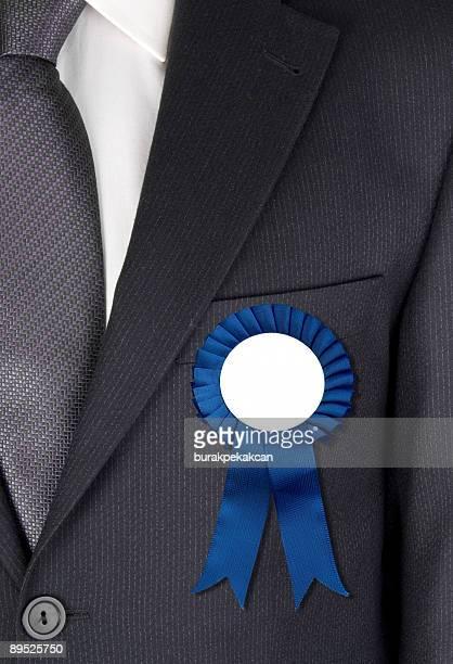 Businessman with blue ribbon attached to his jacket
