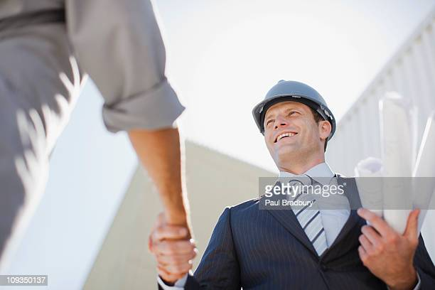 Businessman with blueprints shaking hands with worker