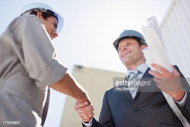 Geschäftsmann mit Werkzeuge beim Händeschütteln mit Arbeiter