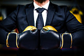 Businessman with boxing gloves is ready for corporate battle. Man in suit, shirt and a tie is holding combat gloves together. Shot in a boxing gym, concept of relentless struggle and success.