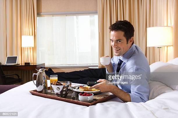 Businessman with breakfast on bed in hotel room