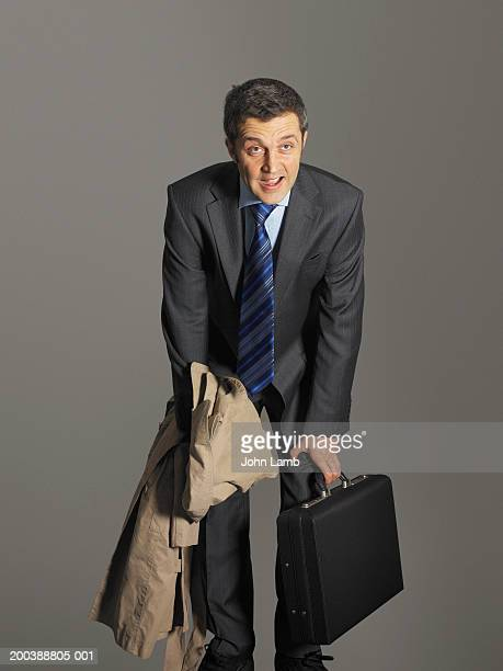 Businessman with briefcase and coat, catching breath, hands on knees