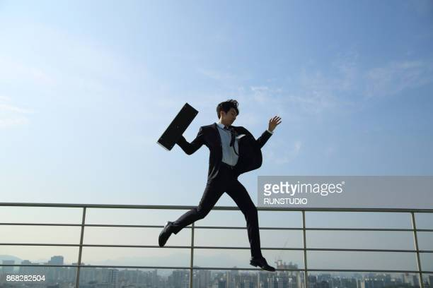 businessman with briefcase jumping