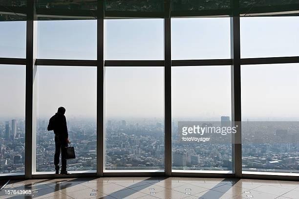 ビジネスマンがブリーフケースを見渡す大きな窓から街の日本