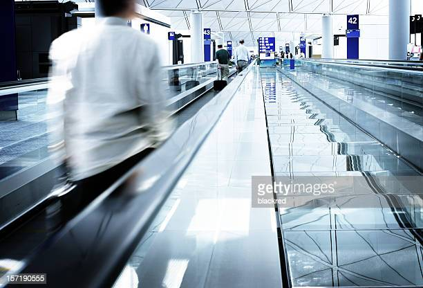 Businessman with briefcase on walkway in airport