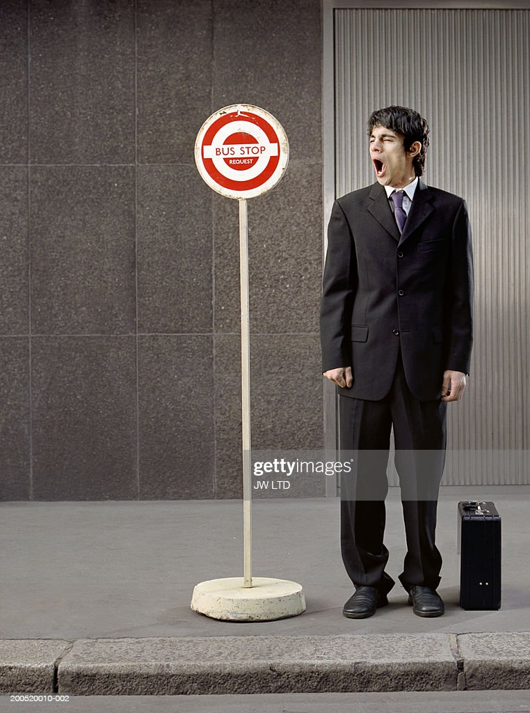 Businessman with briefcase standing at bus stop, yawning : Stock Photo
