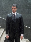 Businessman with briefcase standing on steps in rain, portrait