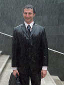 Businessman with briefcase standing on steps in rain, smiling, portrait
