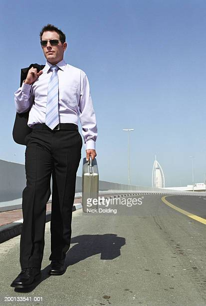 Businessman with briefcase, walking along road, low angle view