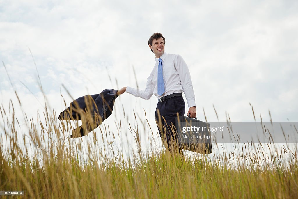 Businessman with briefcase walking through long grass : Stock Photo