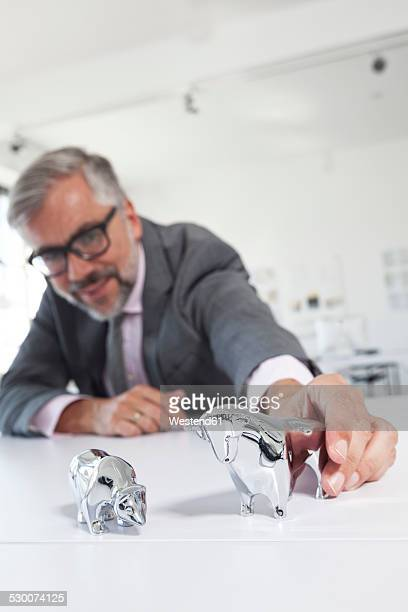 Businessman with bull and bear figurines on his desk