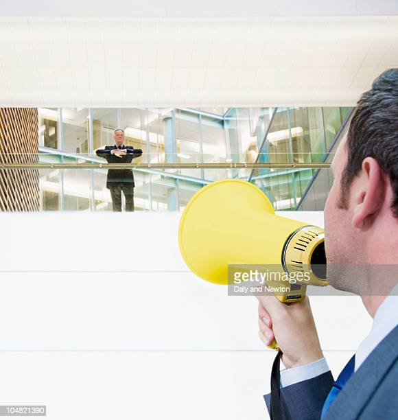 Businessman with bullhorn yelling up at boss