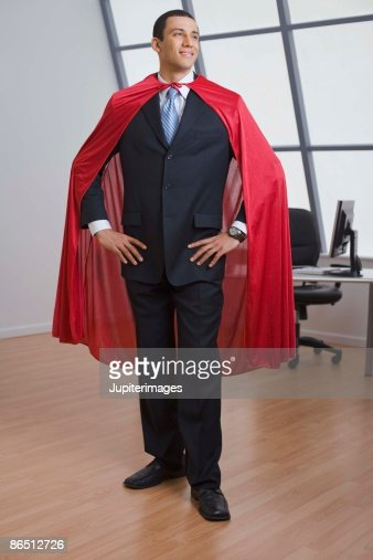 Businessman with cape standing in office