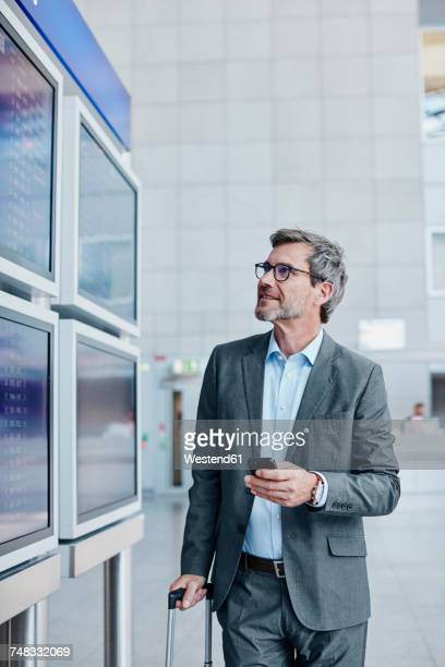 Businessman with cell phone at timetable at the airport