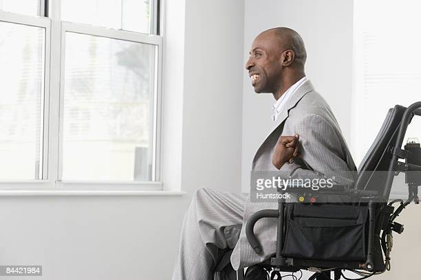 Businessman with Cerebral Palsy looking out through the office window