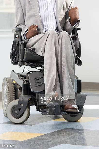 Businessman with Cerebral Palsy moving a motorized wheelchair with his foot