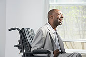Businessman suffering from Cerebral Palsy sitting in a wheelchair and smiling