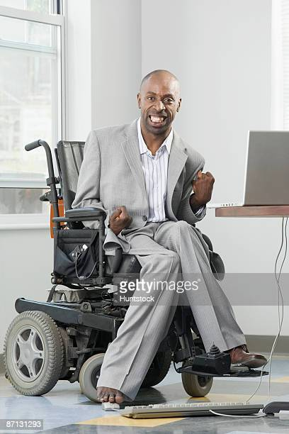 Businessman with Cerebral Palsy working on a computer with his foot