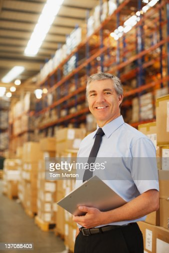 Businessman with clipboard in warehouse : Stock Photo