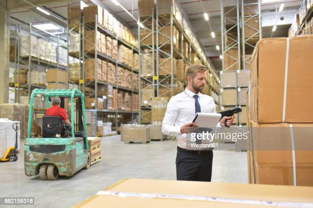 Businessman with clipboard in warehouse scanning goods