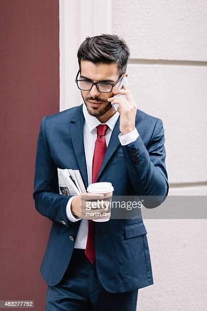 Uomo d'affari con caffè e giornale, al telefono