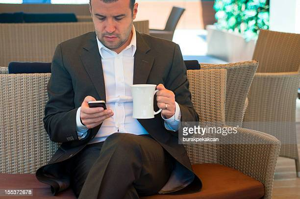 Uomo d'affari con caffè guardando smartphone, Istanbul, Turchia
