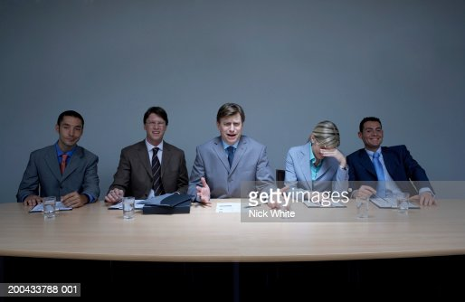 Businessman with colleagues at boardroom table, gesturing with hands