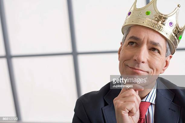 Businessman with crown thinking