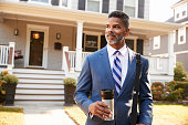 Businessman With Cup Of Coffee Leaving Suburban House For Work