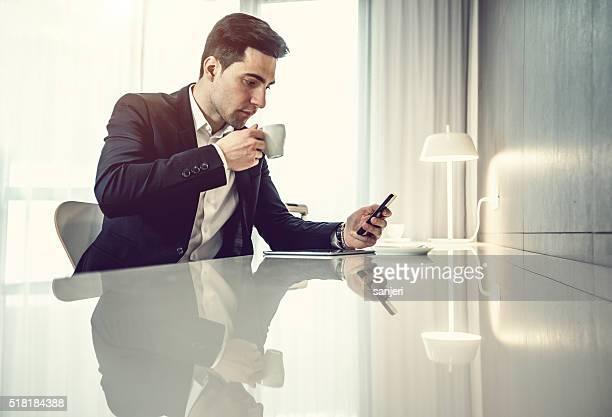 Geschäftsmann mit Digitaltablett und Telefon