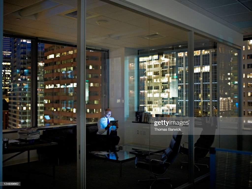 Businessman with digital tablet in office at night : Stock Photo