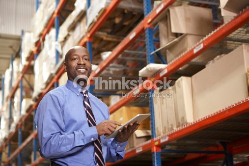 Businessman With Digital Tablet In Warehouse Stock Photo