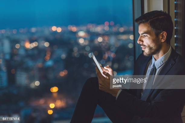 Businessman with digital tablet late in the office