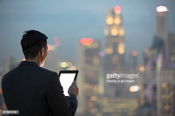 Businessman with digital tablet looking at city