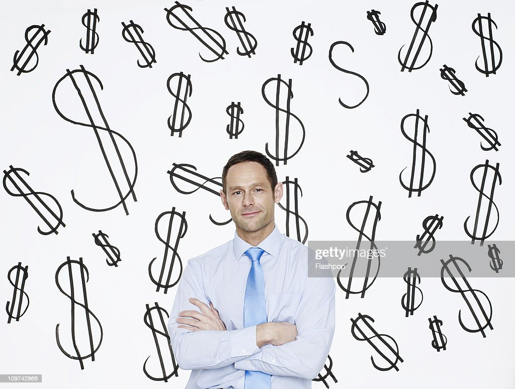 Businessman with dollar signs in the background : Stock Photo