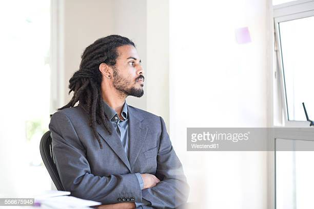 Businessman with dreadlocks looking through window in an office