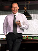 Businessman with drink leaning against pool table.