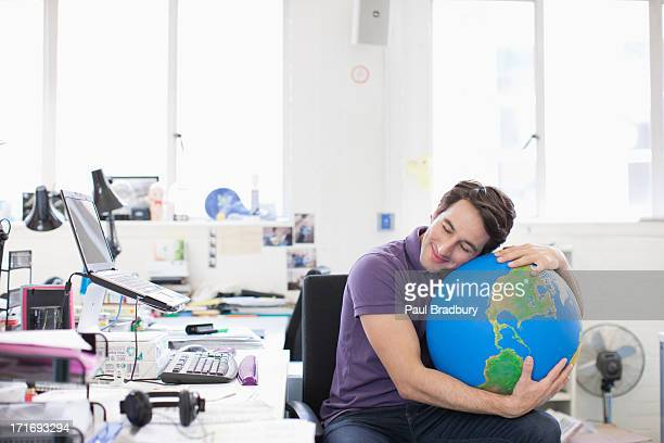 Businessman with eyes closed hugging globe at desk in office