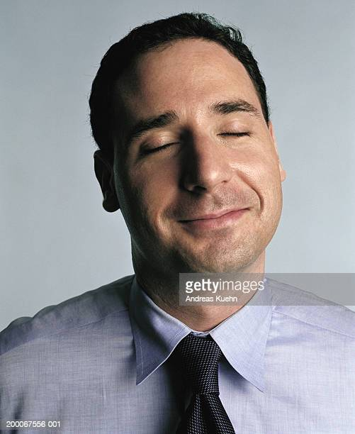 Businessman with eyes closed, smiling, close up